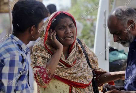 Woman mourns while talking on cell phone after she identified a body of her family member, who was killed in the Friday's plane crash, at a morgue in Karachi, Pakistan, . An aviation official says a passenger plane belonging to state-run Pakistan International Airlines carrying passengers and crew has crashed near the southern port city of Karachi