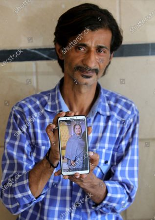 Pakistani Shahid Ahmed shows the picture of his mother Irshad Begum, who was killed in the Friday's plane crash, on his mobile phone outside a morgue in Karachi, Pakistan, . An aviation official says a passenger plane belonging to state-run Pakistan International Airlines carrying passengers and crew has crashed near the southern port city of Karachi