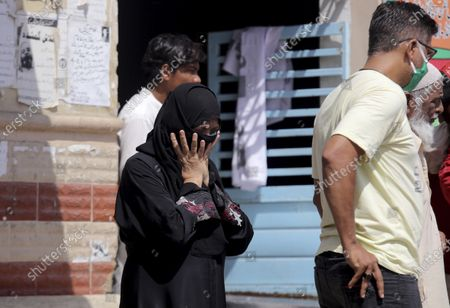 Woman arrive to identify body of her family member who was killed in the Friday's plane crash, at a morgue in Karachi, Pakistan, . An aviation official says a passenger plane belonging to state-run Pakistan International Airlines carrying passengers and crew has crashed near the southern port city of Karachi