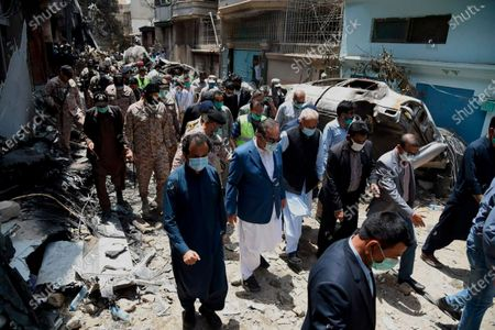 In this photo released by Pakistan Civil Aviation Authority, provincial governor Imran Ismail, center in blue coat, and Pakistan's aviation minister Ghulam Sarwar, center in black waistcoat, visit the site of Friday's plane crash, in Karachi, Pakistan, . A passenger plane belonging to state-run Pakistan International Airlines carrying passengers and crew crashed Friday near the southern port city of Karachi