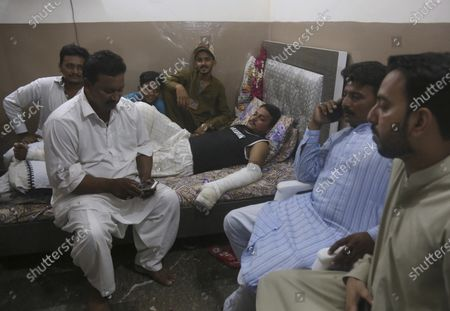 """Relatives visit with Mohammad Zubair, a passenger who survived a plane crash, at his home in Karachi, Pakistan, . When the plane jolted violently, Zubair thought it was turbulence. Then the pilot came on the intercom to warn that the landing could be """"troublesome."""" Moments later, the Pakistan International Airlines flight crashed into a crowded neighborhood near Karachi's international airport"""