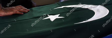 A relative of places his hand on the flag wrapped coffin containing body of Major Sheharyar, a victim of plane crash, during his funeral, a day after a passenger plane of state run Pakistan International Airlines, crashed in a residential colony, in Karachi, Pakistan, 23 May 2020. A Pakistan International Airlines passenger flight with over 100 people on board crashed on 22 May as it was preparing to land in the port city of Karachi. According to media reports at least 97 people died in the accident.