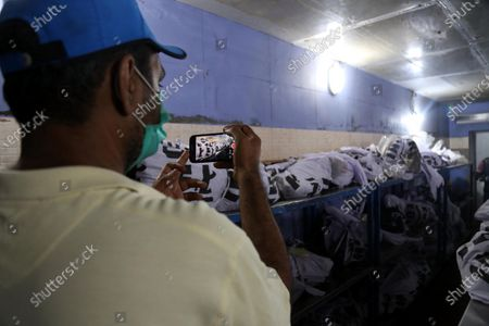 A man takes picture of the bodies of the victims the day after a passenger plane of state run Pakistan International Airlines crashed in a residential area, at a mortuary in Karachi, Pakistan, 23 May 2020. A Pakistan International Airlines passenger flight with over 100 people on board crashed on 22 May as it was preparing to land in the port city of Karachi. According to media reports at least 97 people died in the accident.