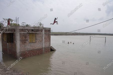 A boy is jumping into a field full of water which used to be a playground before the super cyclone Amphan hit.