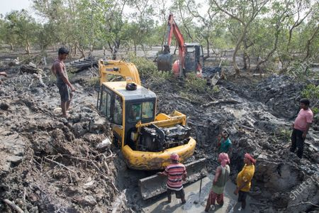 Rescue team trying to pull out a bulldozer which got stuck while working at a destroyed dam of Sunderbans mangrove during the super cyclone.