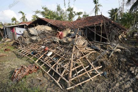 A woman salvages her belongings from her house damaged due to Cyclone Amphan, at Kakdwip in the Sunderbans, South 24 Parganas district, on May 22, 2020 in Kakdwip, India.