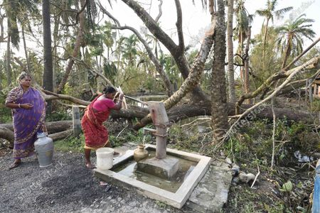 Women fill water from a handpump after their local pond was filled with saline water that has killed fresh water fish and was brought upstream due to Cyclone Amphan, at Kakdwip in the Sunderbans, South 24 Parganas district, on May 22, 2020 in Kakdwip, India.