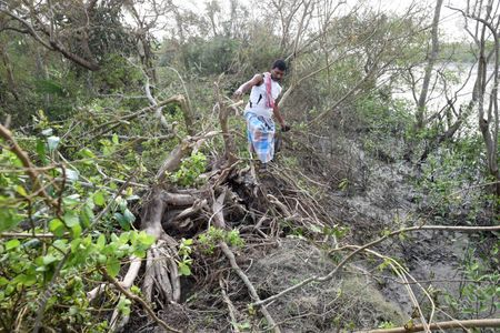 A man crosses an embankment damaged due to Cyclone Amphan, at Kakdwip in the Sunderbans, South 24 Parganas district, on May 22, 2020 in Kakdwip, India.
