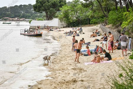"""People take advantage of the beaches, chill, lie on towels  and tan in the sun despite the """"dynamic beach"""" obligation, at Les Jacquets beach in Cap Ferret"""