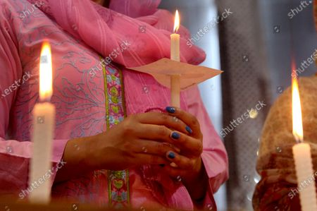 Christian women hold candles during a prayer service for the victims of Friday's plane crash, at St. Johan Cathedral in Peshawar, Pakistan, . A Pakistan International Airlines carrying passengers and crew has crashed near the southern port city of Karachi