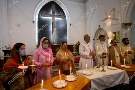 Christians hold candles during a prayer service for the victims of a plane crash, at St. Johan Cathedral in Peshawar, Pakistan, . A Pakistan International Airlines carrying passengers and crew has crashed near the southern port city of Karachi on Friday