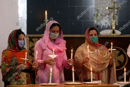 Christian women hold candles during a prayer service for the victims of a plane crash, at St. Johan Cathedral in Peshawar, Pakistan, . A Pakistan International Airlines carrying passengers and crew has crashed near the southern port city of Karachi on Friday