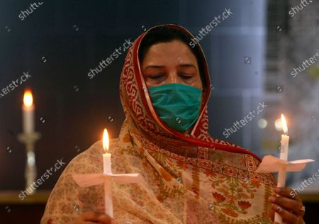Christian woman holds candles during a prayer service for the victims of a plane crash, at St. Johan Cathedral in Peshawar, Pakistan, . A Pakistan International Airlines carrying passengers and crew crashed near the southern port city of Karachi on Friday. (AP Photo/Muhammad Sajjad