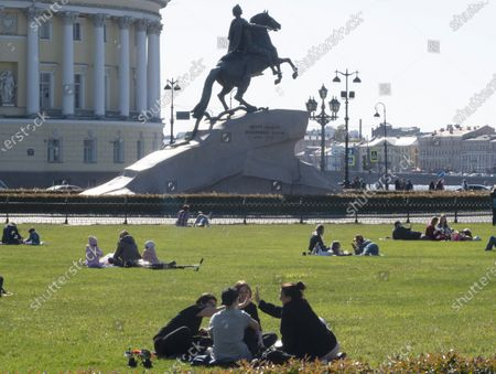 People relax despite the self-isolation regime announced by the authorities due to the coronavirus in St.Petersburg, Russia, . The equestrian statue of Peter the Great known as the Bronze Horseman by French sculptor Etienne Maurice Falconet in the background