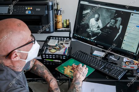 Stock Photo of French tattoo artist Denis, wearing a protective face mask, looks at a photo on his computer of his work with the late French singer Johnny Hallyday at his tattoo shop in Versailles, near Paris, France, 23 May 2020. Tattoo studios and other businesses have to apply strict sanitary rules to reopen shops after two months of containment due to the ongoing pandemic of the COVID-19 disease caused by the SARS-CoV-2 coronavirus. France has started to ease COVID-19 lockdown restrictions to restart the economy and help people get back to their daily routines.