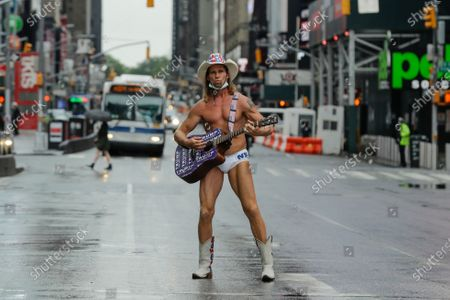 Robert Burck, who performs as the Naked Cowboy, poses for photographs in Times Square during the coronavirus pandemic, in New York