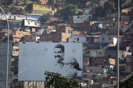 Stock Photo of Billboard, backdropped by the Catia neighborhood, promotes an image of Venezuelan President Nicolas Maduro and first lady Cilia Flores in Caracas, Venezuela, . Bruised by years of economic calamity and more recently by U.S. sanctions, Maduro appealed for international help to deal with the new coronavirus pandemic in March even before the country's first confirmed case