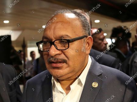 Papua New Guinea's Prime Minister Peter O'Neill is chased by reporters after reading his statement at the end of the APEC 2018 summit at Port Moresby, Papua New Guinea. O'Neill was arrested and taken in for questioning over misappropriation and corruption involving the purchase of two generators from Israel. O'Neill was arrested by police at Jackson's International Airport in Port Moresby after flying back from Brisbane, Australia, where he had been stranded because of COVID-19 lockdowns. He was later released on bail and will spend two weeks in isolation at his home due to the same virus restrictions