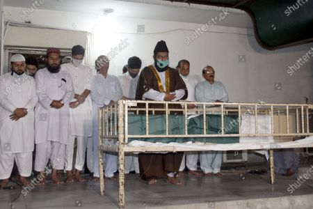 """(EDITOR'S NOTE: Image depicts death) Pakistani relatives and others offering funeral prayer to pilot Captain Sajjad Gull who was died in plane crash PK 8303, a day after a Pakistan International Airlines aircraft crashed in a residential area in Karachi"""" in Lahore. One of the two people to survive a plane crash in Pakistan that killed 97 people has described jumping from the burning wreckage of the aircraft after it hurtled into a residential neighborhood."""