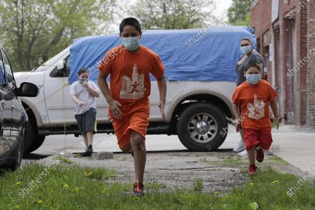 Mariano Ochoa, 9, second from left, and his brother Jesus Ochoa, 5, front right, run in front of their home as their mother Mariana Ochoa, back right, and brother Victor Ochoa, 7, left, watch in Chicago, . Chicago Run's at-home fitness programs have become an essential part of the family's routine during the coronavirus pandemic