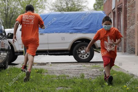 Stock Photo of Mariano Ochoa, 9, left, and his brother Jesus Ochoa, 5, run in front of their home in Chicago, . Mariana Ochoa has three young boys, ages 9, 7, and 5, and Chicago Run's at-home fitness programs have become an essential part of the family's routine during the coronavirus pandemic