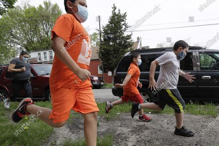Brothers Victor Ochoa, 7, right, Jesus Ochoa, 5, second from right, Mariano Ochoa 9, second from left, and their mother Mariana Ochoa run in front of their home in Chicago, . Chicago Run's at-home fitness programs have become an essential part of the family's routine during the coronavirus pandemic
