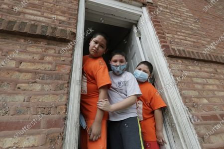 Mariano Ochoa, 9, left, poses for photo with his brothers Victor Ochoa, 7, center, Jesus Ochoa, 5, at their home in Chicago, . Mariana Ochoa has three young boys, ages 9, 7, and 5, and Chicago Run's at-home fitness programs have become an essential part of the family's routine during the coronavirus pandemic