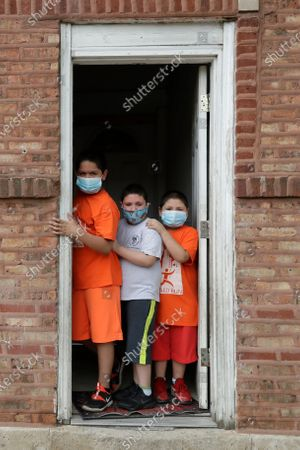 Stock Image of Mariano Ochoa, 9, left, poses for a photo with his brothers Victor Ochoa, 7, center, Jesus Ochoa, 5, at their home in Chicago, . Chicago Run's at-home fitness programs have become an essential part of the Ochoa family's routine during the coronavirus pandemic