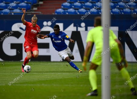 Augsburg's Tin Jedvaj, left, duels for the ball with Schalke's Rabbi Matondo during the German Bundesliga soccer match between FC Schalke 04 and FC Augsburg at the Veltins-Arena in Gelsenkirchen, Germany, . The German Bundesliga becomes the world's first major soccer league to resume after a two-month suspension because of the coronavirus pandemic