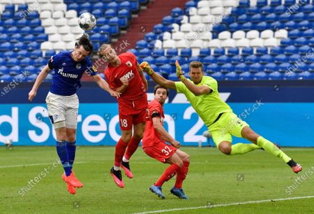 Schalke's Michael Gregoritsch, left, challenges for the ball with Augsburg's Tin Jedvaj, center, and Augsburg's goalkeeper Andrea Luthe, right, during the German Bundesliga soccer match between FC Schalke 04 and FC Augsburg at the Veltins-Arena in Gelsenkirchen, Germany, . The German Bundesliga becomes the world's first major soccer league to resume after a two-month suspension because of the coronavirus pandemic