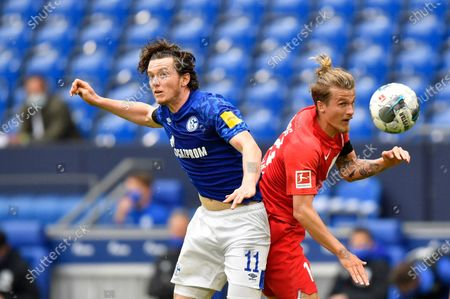 Schalke's Michael Gregoritsch, left, jumps for the ball with Augsburg's Tin Jedvaj during the German Bundesliga soccer match between FC Schalke 04 and FC Augsburg at the Veltins-Arena in Gelsenkirchen, Germany, . The German Bundesliga becomes the world's first major soccer league to resume after a two-month suspension because of the coronavirus pandemic