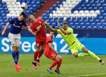 Schalke's Michael Gregoritsch (L) challenges for the ball with Augsburg's Tin Jedvaj (C) and Augsburg's goalkeeper Andrea Luthe (R) during the German Bundesliga soccer match between FC Schalke 04 and FC Augsburg in Gelsenkirchen, Germany, 24 May 2020. The German Bundesliga becomes the world's first major soccer league to resume after a two-month suspension because of the coronavirus pandemic.