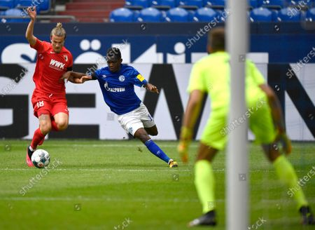 Augsburg's Tin Jedvaj (L) duels for the ball with Schalke's Rabbi Matondo during the German Bundesliga soccer match between FC Schalke 04 and FC Augsburg in Gelsenkirchen, Germany, 24 May 2020. The German Bundesliga becomes the world's first major soccer league to resume after a two-month suspension because of the coronavirus pandemic.