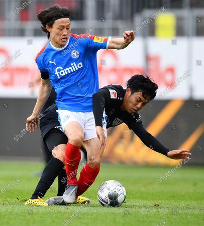 Jae-sung Lee (L) of Kiel is challenged by Wataru Endo of Stuttgart during the Second Bundesliga match between Holstein Kiel and VfB Stuttgart at Holstein-Stadion in Kiel, Germany, 24 May 2020.