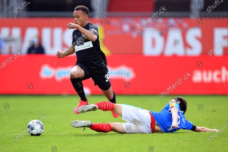 Roberto Massimo (L) ss is challenged by Jae-sung Lee of Kiel during the Second Bundesliga match between Holstein Kiel and VfB Stuttgart at Holstein-Stadion in Kiel, Germany, 24 May 2020.