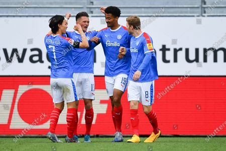 Emmanuel Iyoha (2R) of Kiel celebrates his team's first goal with team mates Alexander Muehling (R), Fabian Reese (2L) and Jae-sung Lee (L)  during the Second Bundesliga match between Holstein Kiel and VfB Stuttgart at Holstein-Stadion in Kiel, Germany, 24 May 2020.