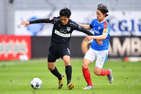 Wataru Endo (L) of Stuttgart is challenged by Jae-sung Lee of Kiel during the Second Bundesliga match between Holstein Kiel and VfB Stuttgart at Holstein-Stadion in Kiel, Germany, 24 May 2020.
