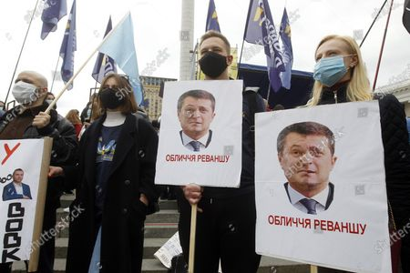 Protesters hold placards with depicted combo portraits of Ukrainian President Volodymyr Zelensky and former Ukrainian President Viktor Yanukovich during a rally of opposition timed to the first year anniversary of Volodymyr Zelensky's presidency. Thousands of people marched from the Independence Square to the Presidential Office during the opposition protest called Stop revanche against the policy of Ukrainian president Volodymyr Zelensky which they consider of being pro-Kremlin and against any concessions to Russia, as local media reported.