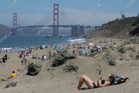 Sara Stewart, foreground, reads a book while away from crowds visiting Baker Beach during the coronavirus outbreak in San Francisco