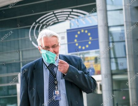 Stock Picture of Member of the European Parliament from the Law and Justice (PiS) Party, former Polish foreign minister Witold Waszczykowski removes his face mask during a press briefing ahead to a debate on determination of a clear risk of a serious breach by the Republic of Poland of the rule of law at European parliament committee on civil liberties, justice and home affairs in Brussels, Belgium 25 May 2020. Today Debate mark also the fourth anniversary of first claim at EU Parliament on rule of Law in Poland.