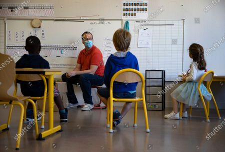 Schoolchildren attend a class while practicing social distancing at the Angela Davis kindergarten and elementary school in Montreuil, France, 25 May 2020. France began an easing of lockdown measures on 11 May amid the ongoing coronavirus COVID-19 pandemic. The gradual return of schoolchildren has presented school establishments with new challenges to implement safe social distancing measures.