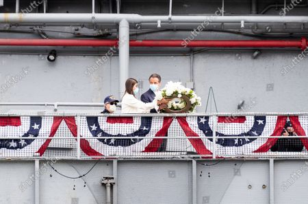 New York Governor Andrew Cuomo (D) and Michaela Kennedy-Cuomo tossing a wreath into the Hudson River as part of the Memorial Day ceremony aboard the USS Intrepid at the Intrepid Sea, Air and Space Museum.
