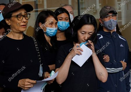 Stock Image of Pansy Ho, center, daughter of Macau tycoon Stanley Ho takes off her face mask as she speaks to the press with Ho's family members outside a hospital, Hong Kong, . Stanley Ho, the dashing billionaire and bon vivant who was considered the father of modern gambling in China, has died, his daughter Pansy Ho said Tuesday. He was 98