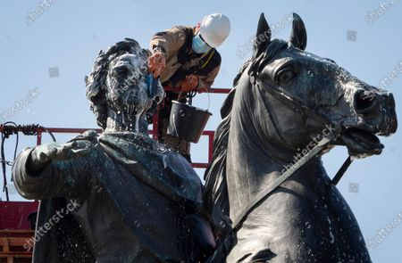 Worker wearing a face mask to protect against coronavirus washes a city landmark, the equestrian statue of the Russian Tsar Peter the Great known as the Bronze Horseman by French sculptor Etienne Maurice Falconet, in St.Petersburg, Russia