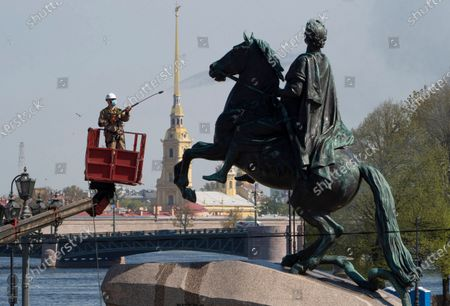 Stock Image of Worker wearing a face mask to protect against coronavirus washes a city landmark, the equestrian statue of the Russian Tsar Peter the Great known as the Bronze Horseman by French sculptor Etienne Maurice Falconet, in St.Petersburg, Russia