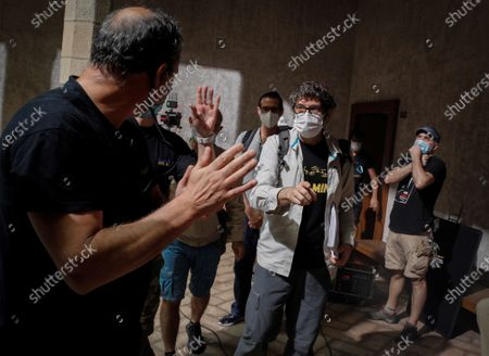The director of the series 'Tres Caminos' (lit. Three Ways), Norberto Lopez (C), chats with members of his team while wearing facial protective masks during the filming of the Amazon Prime Video, Ficcion Producciones and Beta Films joint production at Condestable Palace in Pamplona, Spain, 26 May 2020. The series narrates the story of five people of different nationalities that become friends as they walk St James' Way.