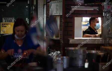 Stock Photo of Chef Miguel Barrow, right, and bartender Julie Radtke, left, prepare food to-go at Kelly's Korner on Saturday, May 16, 2020 in Placentia, CA. The sports bar is effectively grounded as the pandemic shutdowns affecting all restaurants limit him to take-out. Like most restaurants and bars, Kelly's has had to pivot drastically to survive.