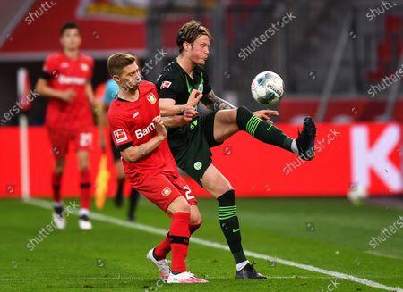 Mitchell Weiser (L) of Leverkusen in action against Wout Weghorst (R) of Wolfsburg during the German Bundesliga soccer match between Bayer Leverkusen and VfL Wolfsburg in Leverkusen, Germany, 26 May 2020.