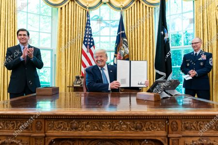 Stock Picture of Donald Trump, joined by Department of Defense Secretary Mark Esper and US Space Force Senior Enlisted Advisor CMSgt Roger Towberman, signs an Armed Forces Day Proclamation, in the Oval Office of the White House.