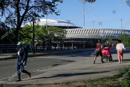 Pedestrians wear protective masks during the coronavirus pandemic as they walk past the USTA Billie Jean King National Tennis Center in Flushing Meadows Corona Park, in the Queens borough of New York
